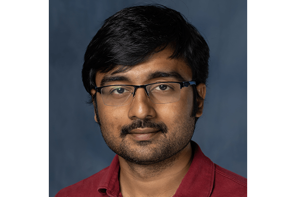 Portrait of Post-Doctoral researcher, Pratik Pal. He wear thin black rimmed glasses and a red polo.