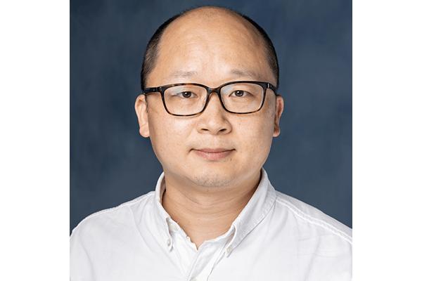 Portrait of Zheng lab technician, Peiyi Zhang. He is wearing tortoise shell eyeglasses and wearing a crisp, white collared shirt.