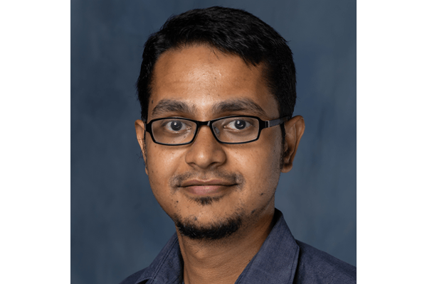 Portrait of second year graduate student Saikat Poddar. He is wearing glasses and wearing a medium navy colared shirt.