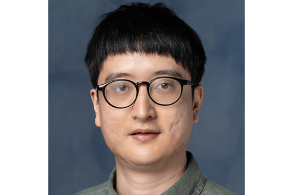 Portrait of post-doctoral researcher, Yufeng Xiao. He has near oval shaped black rimmed glassed and and khaki colared shirt.