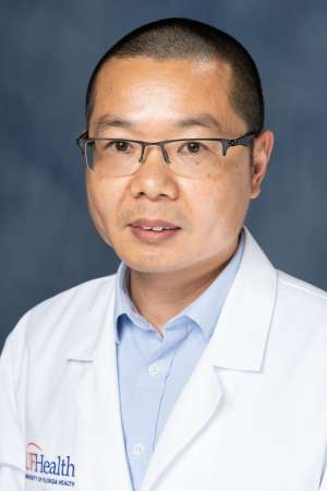 Professional portrait of Dr. Zhixing Wu. He is wearing a crisp, white UF Health lab coats and thinly rimmed black glasses. His hair is shaved short.