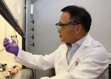 Dr. Zheng works at a chemistry work bench examing a flask. He wears protective eye gear and gloves while sporting a crisp, white lab coat.